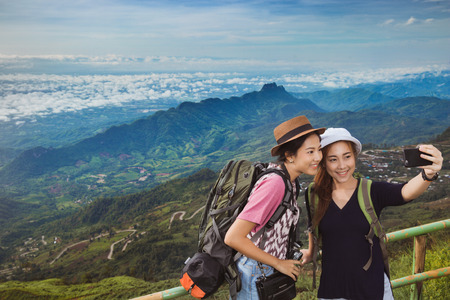Asian tourists are enjoying the selfie with friends. They have come to the mountains of Phu Tubberk Standard-Bild