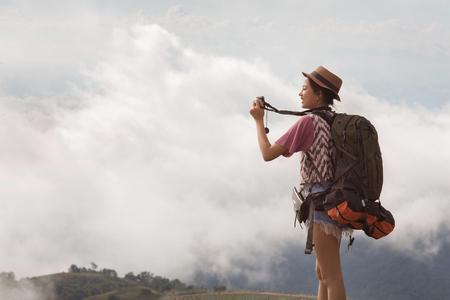 Woman traveling backpack her photography morning fog. Standard-Bild