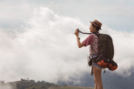 Woman traveling backpack her photography morning fog. Banco de Imagens