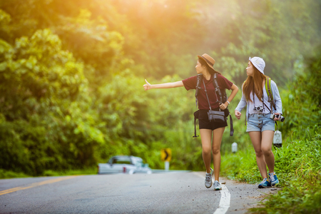 The tourist asian women travel in the middle of nature the car was stopped she will hook up with Stock Photo