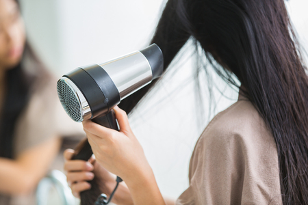 Woman with a hair dryer to heat the hair. Archivio Fotografico