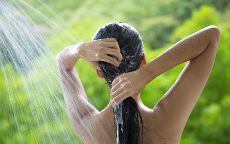 Woman showering and shampooing outdoor