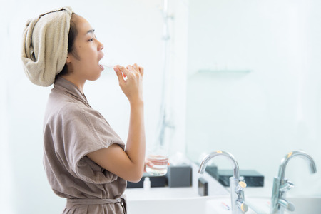 Asian women are brushing teeth in the morning to the bathroom