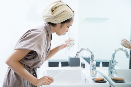 Asian women are mouthwash after brushing teeth in the bathroom. 版權商用圖片 - 81778661