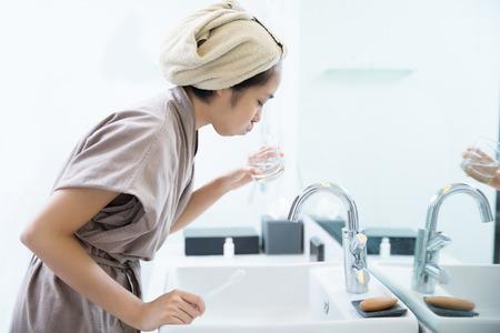Le donne asiatiche sono il colluttorio dopo aver spazzolato i denti in bagno. Archivio Fotografico - 81778661