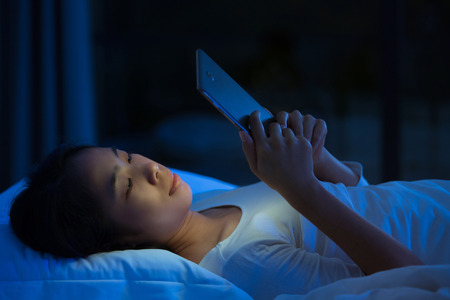 Asian women are using the tablet on the bed before she sleeping at night. Mobile addict concept.