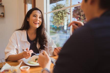 アジアの女性は、朝は、レストランで食べています。