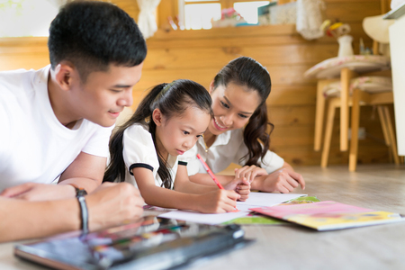 Father and mother Teaching children to do their homework at home Stock Photo - 81857613