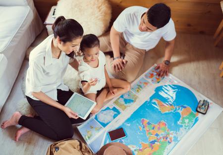 Famiglia asiatica stanno progettando intorno al mondo. il simbolo del fuoco di messa a fuoco è portando un bambino Archivio Fotografico - 81857616