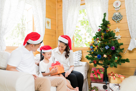 Famille asiatique ouvrant une boîte cadeau le jour de Noël heureux Banque d'images - 81837892
