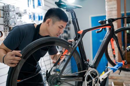 기술자는 상점 판매점에서 자전거를 수리하고 있습니다. 스톡 콘텐츠