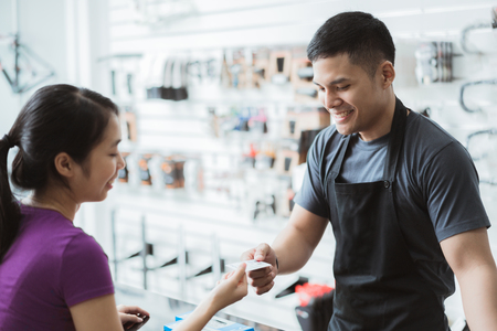 Aziatische vrouwen winkelen in een fietsartikelenwinkel. Met creditcard