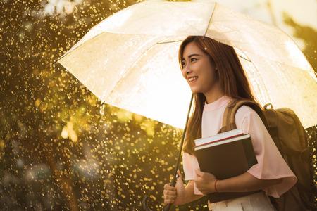 아시아 학생 비가 기다리고, 그녀는 우산을했다.