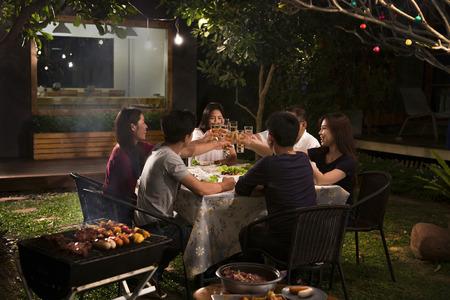Cena, barbacoa y cerdo asado en la noche Foto de archivo - 84957486