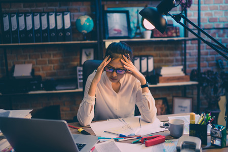 Asian women are stressed out of work. She is in the office at night Stock Photo