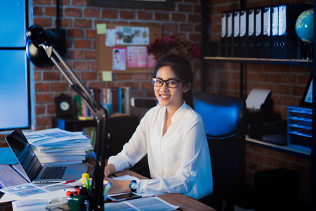 Asian women are working. She is in the office at night