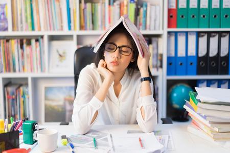 アジアの女性彼女は試験を読むの疲れていた