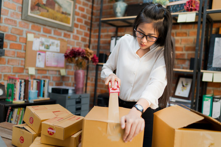 Business woman are packing boxes to send to customers. Imagens