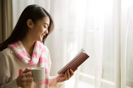 Asian woman reading a book and drinking coffee in the morning.