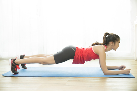 "Asian women are exercising at home.She is pretending to be ""plank"""