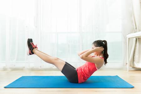 Las mujeres asiáticas hacen ejercicio en casa. Ejercicios abdominales. Sentaos. Foto de archivo - 85778671