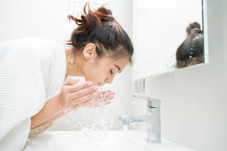 De vrouw wordt wakker van slaap en ze reinigde de ochtend voor de douche