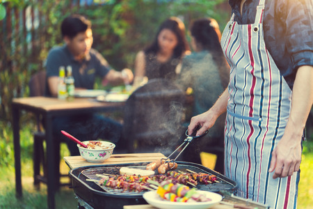 Asian men are cooking for a group of friends to eat barbecue Stock Photo