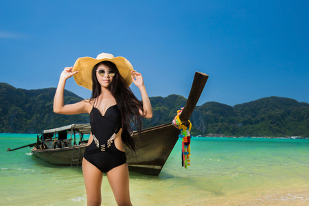 Asian women Standing on the beach Behind her, the boat for transport to the island of Phi Phi, Krabi, Thailand.