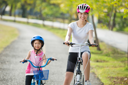 Mother and daughter are biking to the park