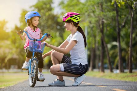La madre de familia asiática enseñando a los niños a andar en bicicleta en el parque