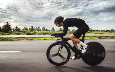 Aziatische mannen fietsen 's ochtends een tijdritfiets Stockfoto