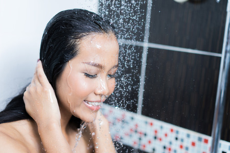 Asian women are taking a shower in the bathroom she is rubbing soap,she is happy and relaxed.