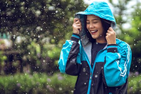 屋外でレインコートを着たアジア人女性。彼女は幸せです。