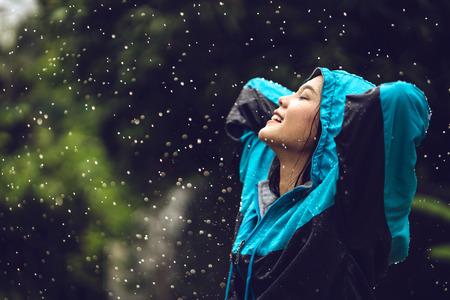 아시아 여자 비옷 야외에서 입고입니다. 그녀는 행복하다. 스톡 콘텐츠