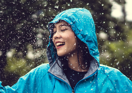 Asian woman wearing a raincoat outdoors. She is happy. Stockfoto