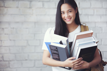 Asian students holding books at university 版權商用圖片 - 94807024