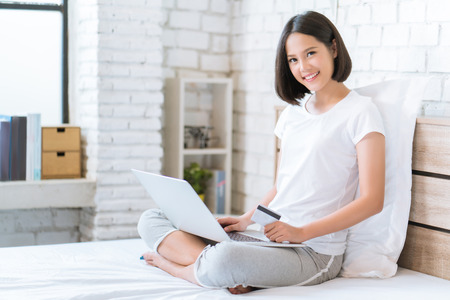 Asian women buy online Using credit card she is in bed Reklamní fotografie - 94681128