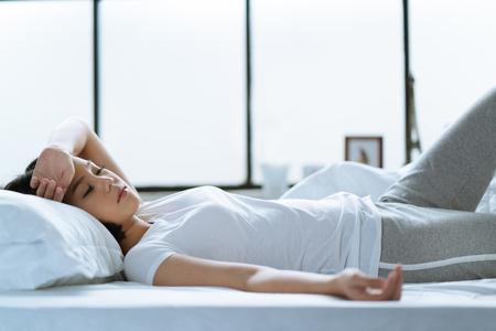 Azjatycka dziewczyna jest bólem głowy w łóżku.
