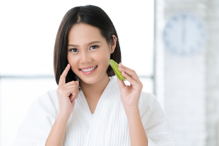 Asian women are using Aloe Vera on her face in the bathroom.
