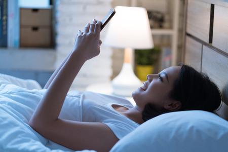 Aziatische vrouwen gebruiken de smartphone op het bed voordat ze 's nachts slaapt. Mobiel verslaafde concept.