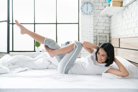 Asian women exercising in bed in the morning, she feels refreshed. Banque d'images