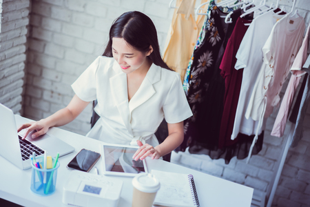 Online traders selling clothes using a calculator from a tablet calculates the costs.