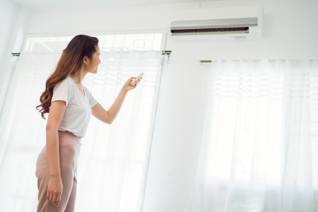 Asian woman Holding Remote Control Air Conditioner In House 写真素材