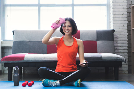 Asian woman wiping her sweat after a workout at home.