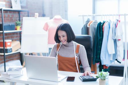 Las ventas en línea están respondiendo las preguntas de los clientes a través de sus computadoras portátiles, haciendo negocios en su hogar. Estaba empujando la calculadora.