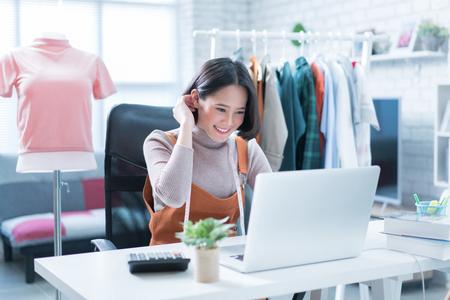 Online verkoop beantwoordt vragen van klanten via hun laptops en doet zaken in haar huis. Stockfoto - 97716651