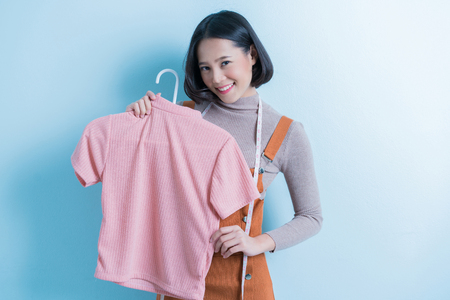 Asian girl designer is showing off the shirt she is designing.