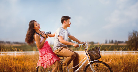 Couples are cyclists relax in the evening the woman was holding a camera to take pictures. Stock Photo