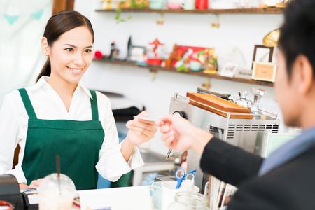 バリスタはレストランでコーヒーを入れています。そして、彼女はクレジットカードをスワイプしているコーヒーショップを所有しています。顧客