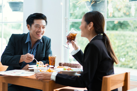 Asian businesspeople are on break for lunch at a restaurant. 免版税图像